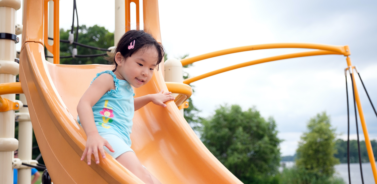 active little toddler girl on the playground 8JNEAR5