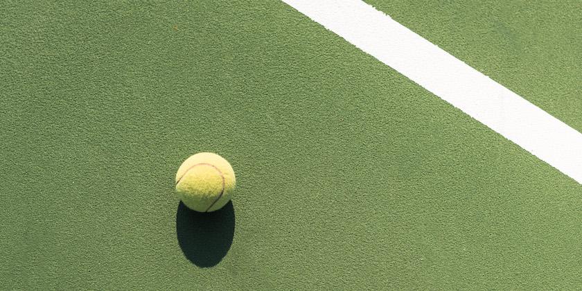 top view of tennis ball on green tennis court UYF3FVD